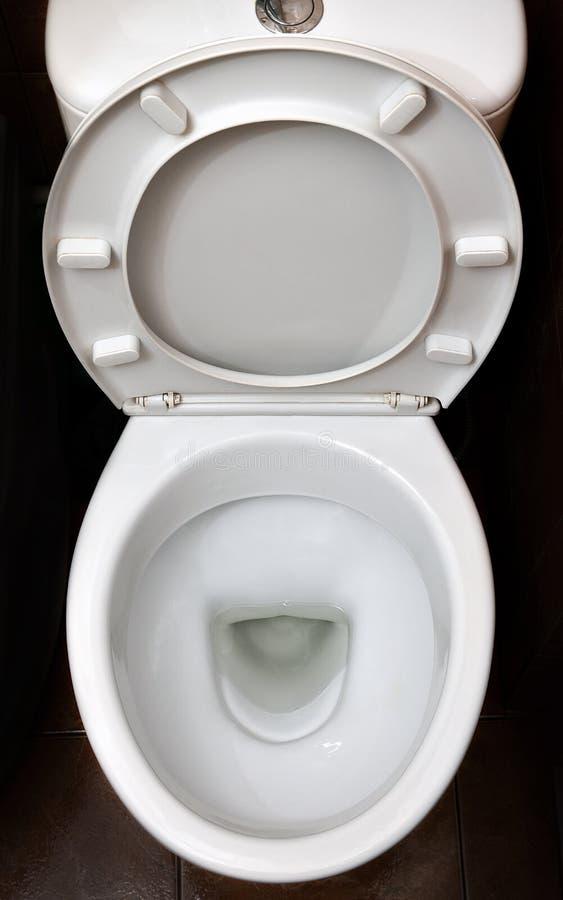 Ett fotografi av en vit keramisk toalettbunke i logen eller badrummet Keramiska sanitära ware för korrigering av nee royaltyfri bild