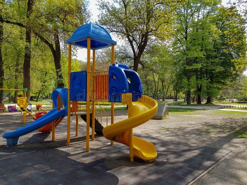 Ett fotografi av glidbanan för barn i stad parkerar arkivbilder
