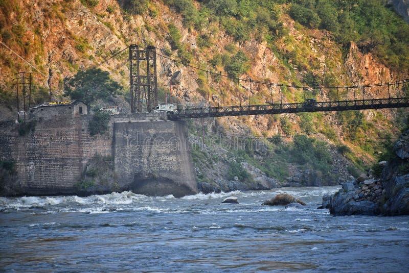 Ett fotografi av ett järn och en träbro över en flod med berget på bakgrund som tidigt på morgonen slår vid solstrålar royaltyfria foton