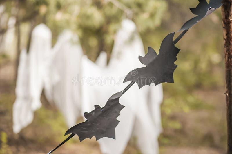 Ett fotoprojekt för allhelgonaafton i natur En girland av svart drog slagträn mot bakgrunden av tre vita spökar i en skog av G royaltyfri bild