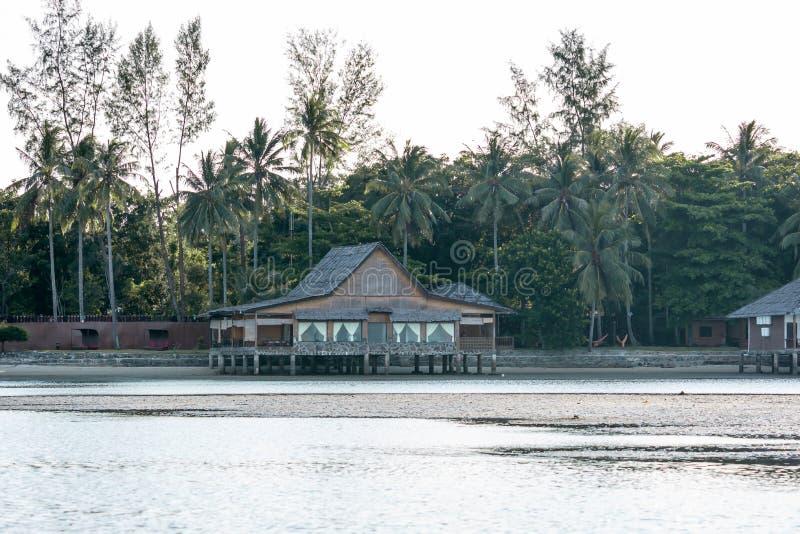 Ett främre område för härlig strand för strandsemesterort som visar stugor, träd och kusten under lågvatten arkivbild
