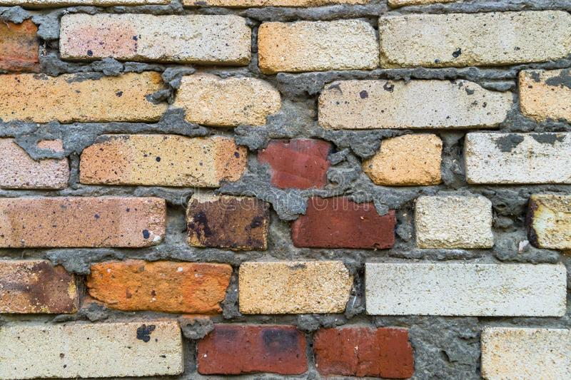 Ett fragment av en gammal tegelstenvägg i orange röda och gula färger Texturera bakgrund royaltyfri bild