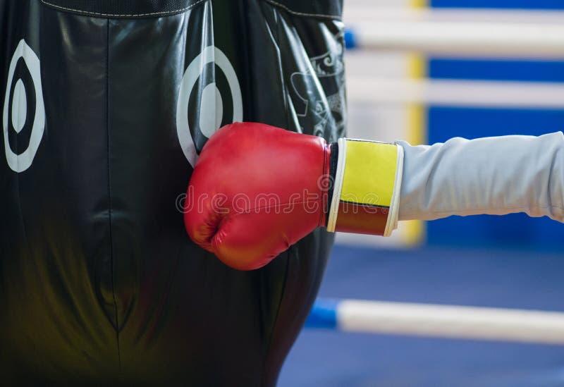 Ett fragment av en hand i en röd handske för boxning slår ett svart päron Th royaltyfri bild