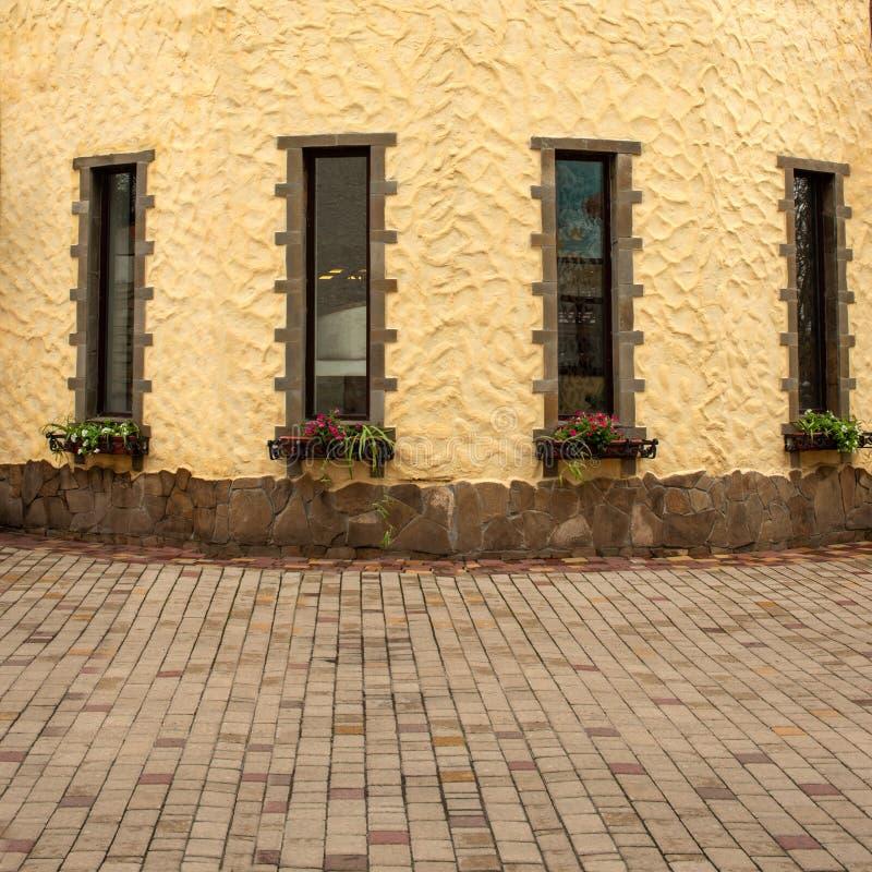 Ett fragment av en stiliserad gul byggnad med två fönster och blommor Byggnaden fodras med kulöra tegelplattor fotografering för bildbyråer