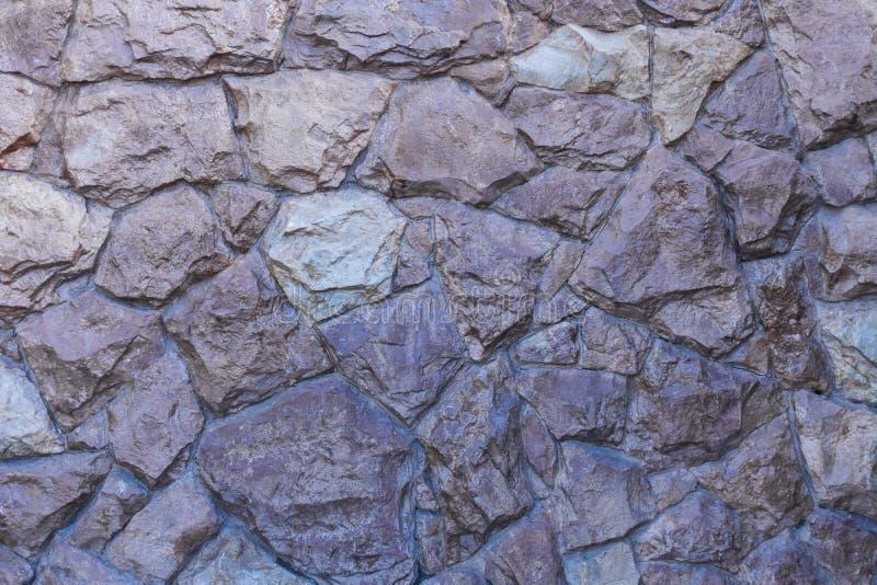 Ett fragment av en vägg av den uncrushed grova stenen som täckas med fernissa arkivbild