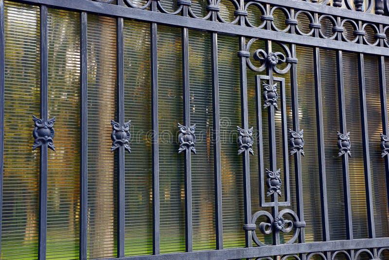 Ett fragment av ett grått staket med falska stänger och en härlig modell royaltyfri fotografi