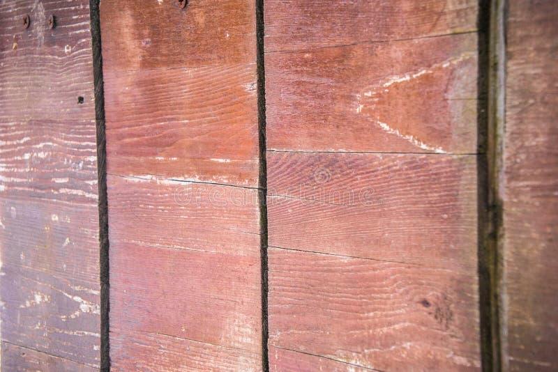 Ett fragment av ett staket som göras av gamla bruna polerade bräden och plankor gammala möjliga något yttersida till trä skriver  arkivbild