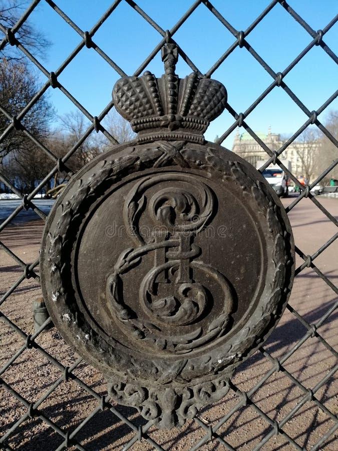 Ett fragment av staketet av parkerar med den kungliga kronan och modellerna royaltyfri foto