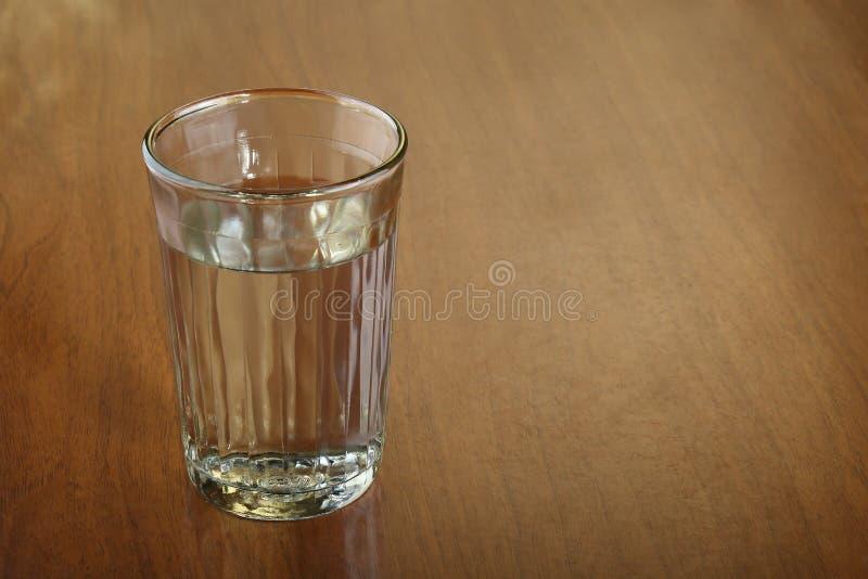 Ett fullt exponeringsglas av vatten av alkohol på den skrapade bruna trätabellen arkivfoton