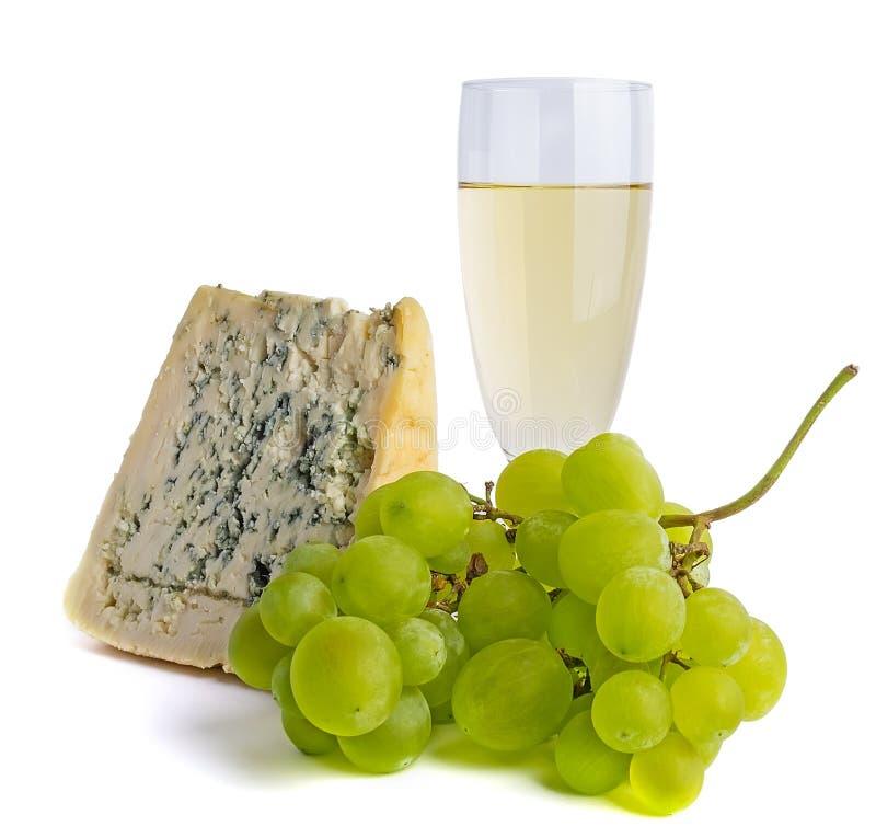 Ett fullt exponeringsglas av vin, en grupp av druvor och ädelost arkivfoto