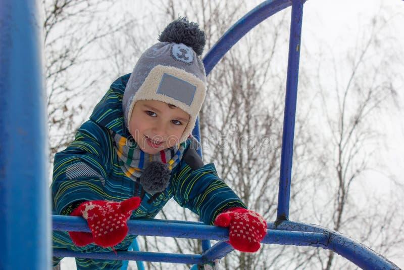 Ett fyraåringbarn, en pojke klättrar trappan på lekplatsen royaltyfria foton