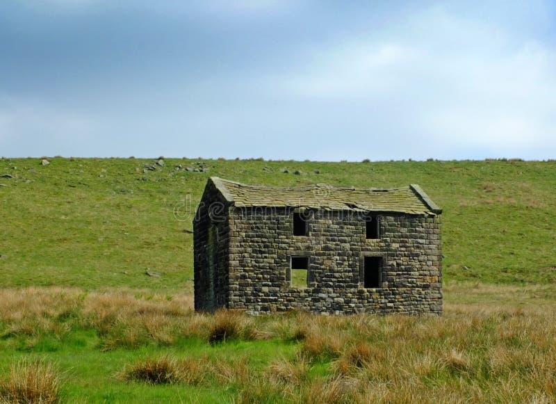 Ett gammalt övergett stenlantbrukarhem i gräsplan betar på hög penninehedland med ljus blå himmel royaltyfri fotografi