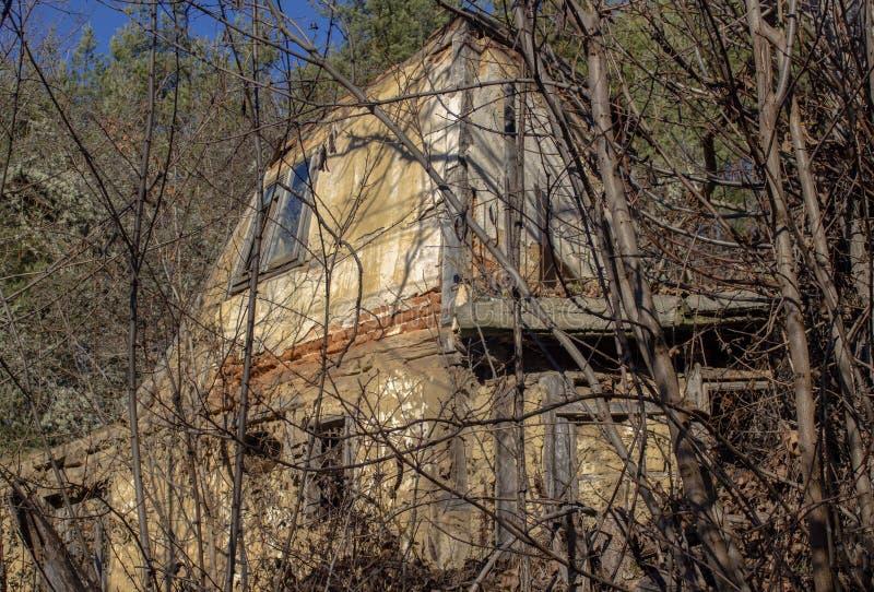 Ett gammalt övergivet hus i en bergsby i vilda träd royaltyfri foto