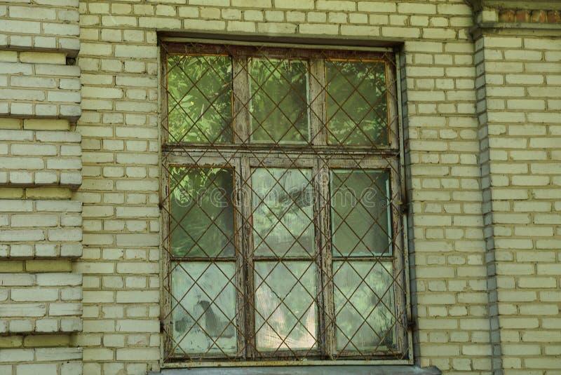 Ett gammalt fönster bak en järnspisgaller på en brun tegelstenvägg royaltyfri bild