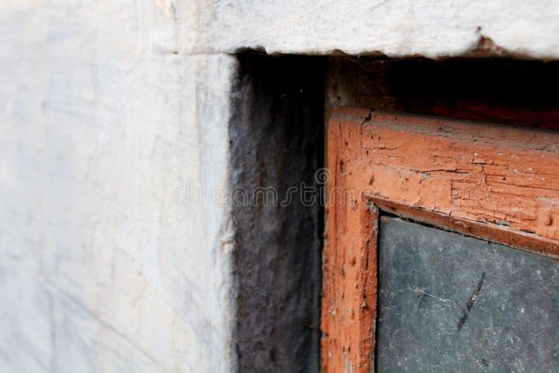 Ett gammalt fönster i en röd ram med smutsigt exponeringsglas på en grå fasad Sikten ?r slutet royaltyfria bilder