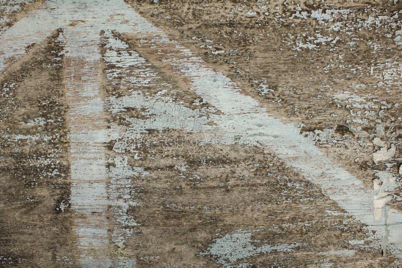 Ett gammalt grått träbräde med sprickor och skalning av blå vit målarfärg naturlig textur för grov yttersida arkivbild