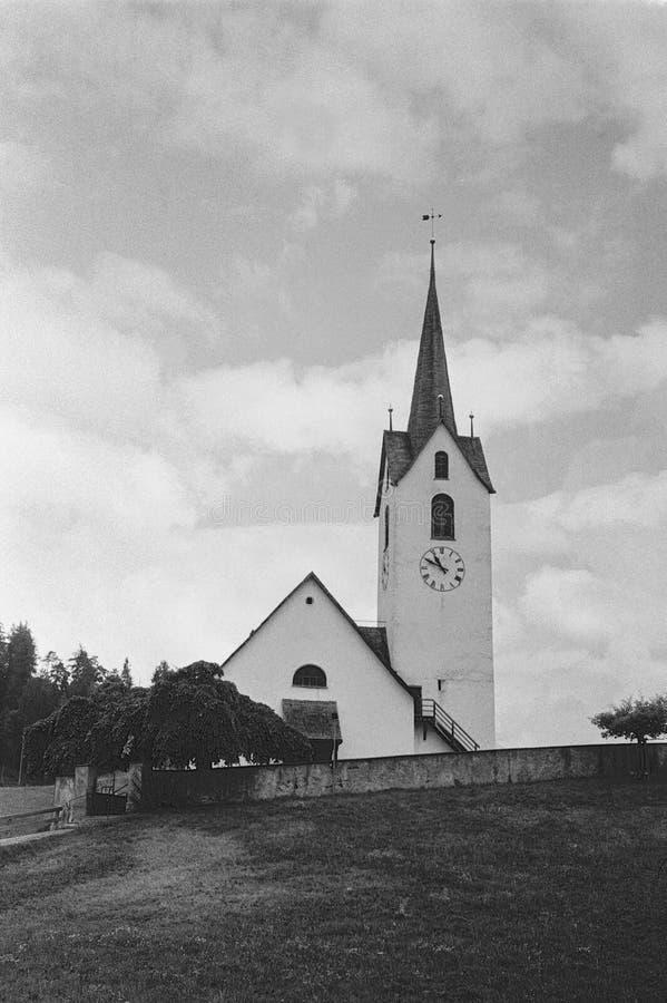 Ett gammalt kapell i byn av Versam i de schweiziska fjällängarna med analogt fotografi - 2 royaltyfri foto