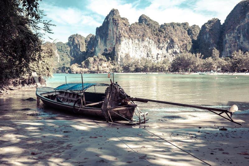 Ett gammalt lång-tailed fartyg som göras av trä på lågvatten Deprimerande färger, tropisk sandig strand fotografering för bildbyråer
