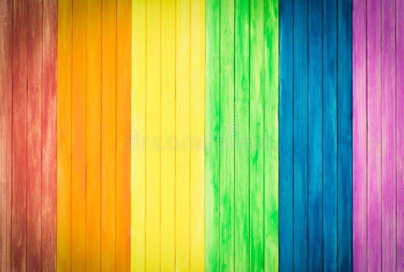 Ett gammalt lantligt träbräde med regnbågen färgar för glad stolthet Gummin royaltyfria bilder