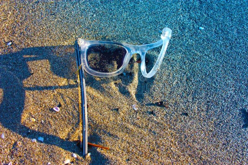 Ett gammalt par av övergett vitt och genomskinligt plast- glasögon lämnade bara på den sandiga stranden brutna objekt och luftför arkivfoto