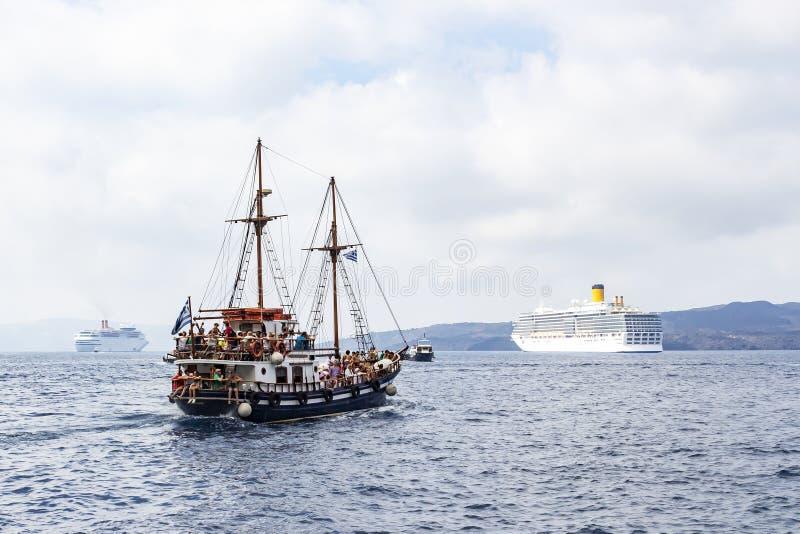 Ett gammalt skepp bredvid flera stora kryssningskepp nära porten av Fira, Santorini, Grekland royaltyfri foto