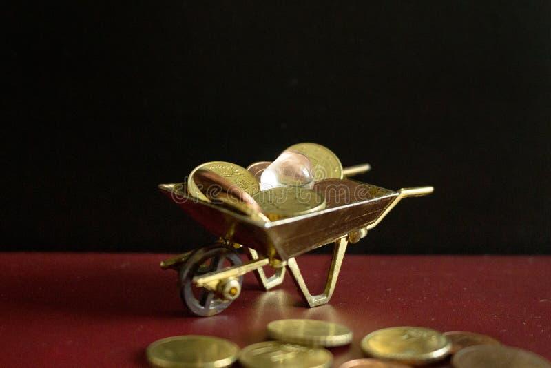 Ett gemstonestycke av den klara kvartskristallen överst av en hög av pengarmynt arkivfoto