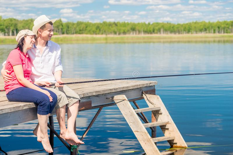 Ett gift par på en pir med kal fot som fångar en fisk arkivfoto