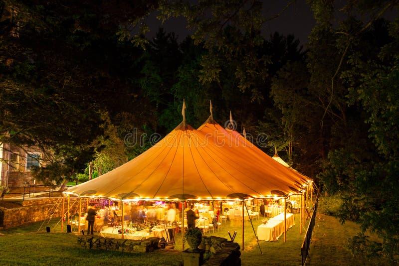 Ett gifta sig tält på natten som omges av träd med ett orange glöd från ljusen, länge exponering - brölloptältserie royaltyfri bild