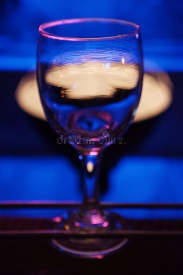 Ett glas vin på bordet med ogenomskinlig klarhet Under blått ljus i en nattklubb arkivfoto