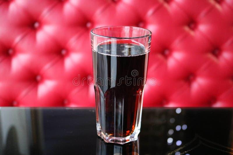 Ett glass exponeringsglas med en brunt, söt, kall kolsyrad drink på en tabell i ett kafé i aftonen på bakgrunden royaltyfria bilder