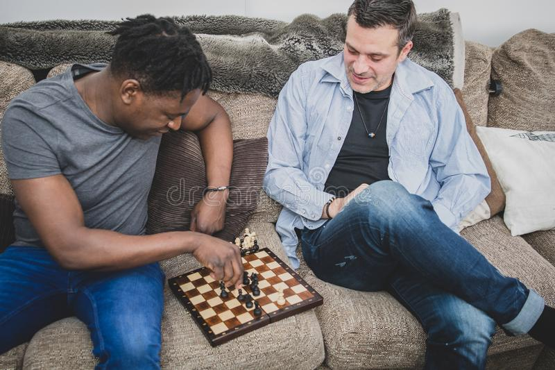 Ett glat par som inomhus tycker om tid hemma och att spela schack royaltyfri bild