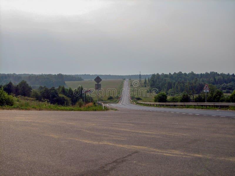 Ett grått band av vägen mellan fält och skogar på en molnig dag royaltyfria foton