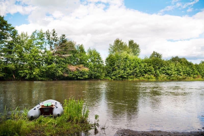 Ett grått uppblåsbart fartyg på flodbanken i vår och sommar royaltyfria foton
