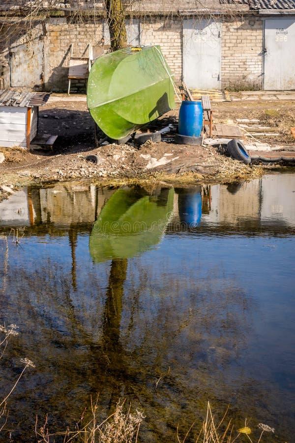 Ett grönt fartyg och en blå trumma och ett träd som reflekterar i vattnet arkivfoto