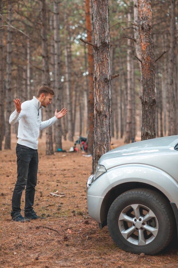 Ett grabbanseende nära en bruten bil och kasta upp händer i frustration i höstskogen arkivfoto