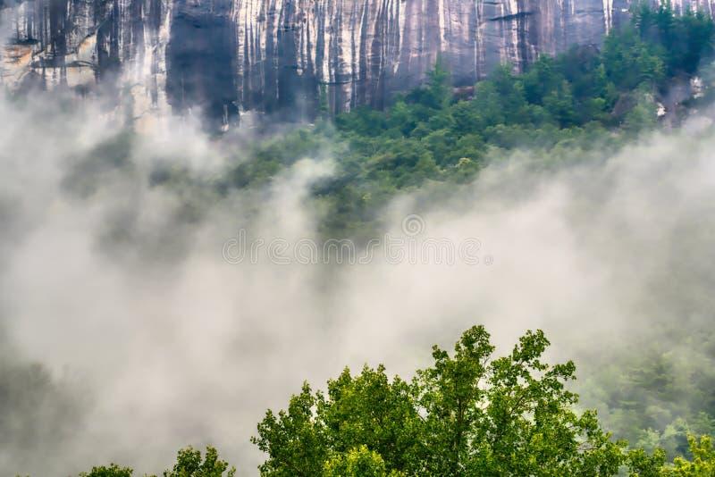 Ett granitberg med höga klippor och låga liggande moln royaltyfri foto