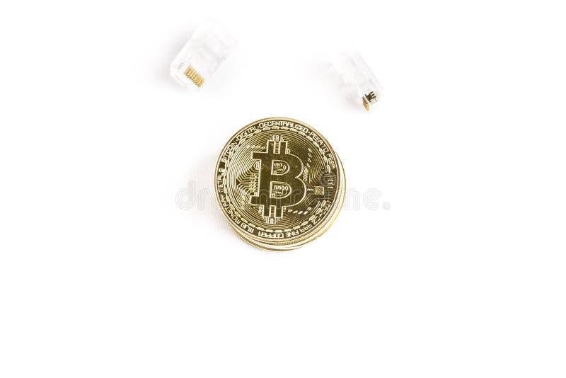 Ett guld- mynt för bitcoin bredvid internetuppkopplingterminaler arkivfoto