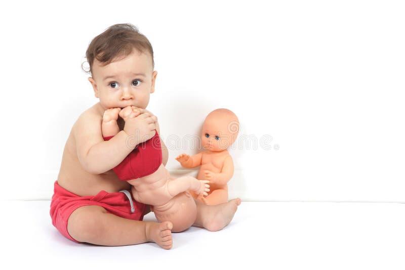 Ett gulligt behandla som ett barn pojkelekar med leksaker och smakar dem royaltyfri foto