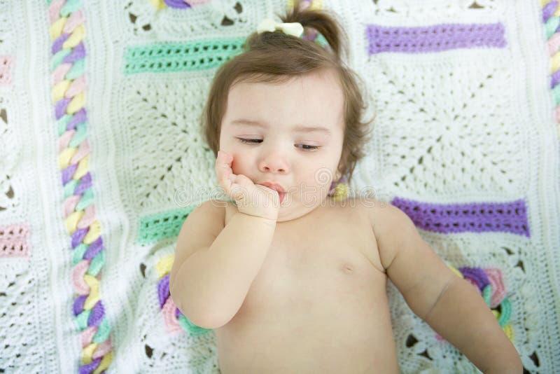 Ett gulligt litet behandla som ett barn flickan suger tummen royaltyfri fotografi