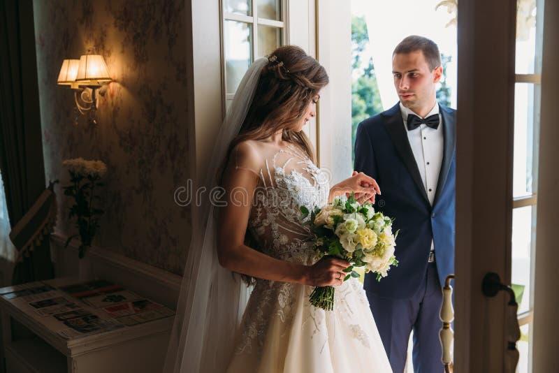 Ett gulligt par av nygifta personer kysser sig händer för ` s Bruden och brudgummen rymmer deras tänder Bruden i en svart royaltyfri bild