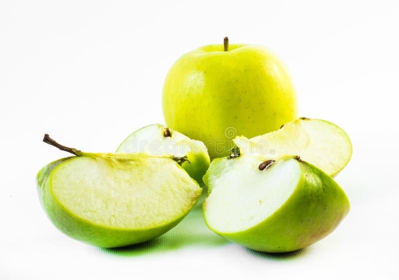 Ett gult äpple och fyra skivor på en vit bakgrund arkivfoton