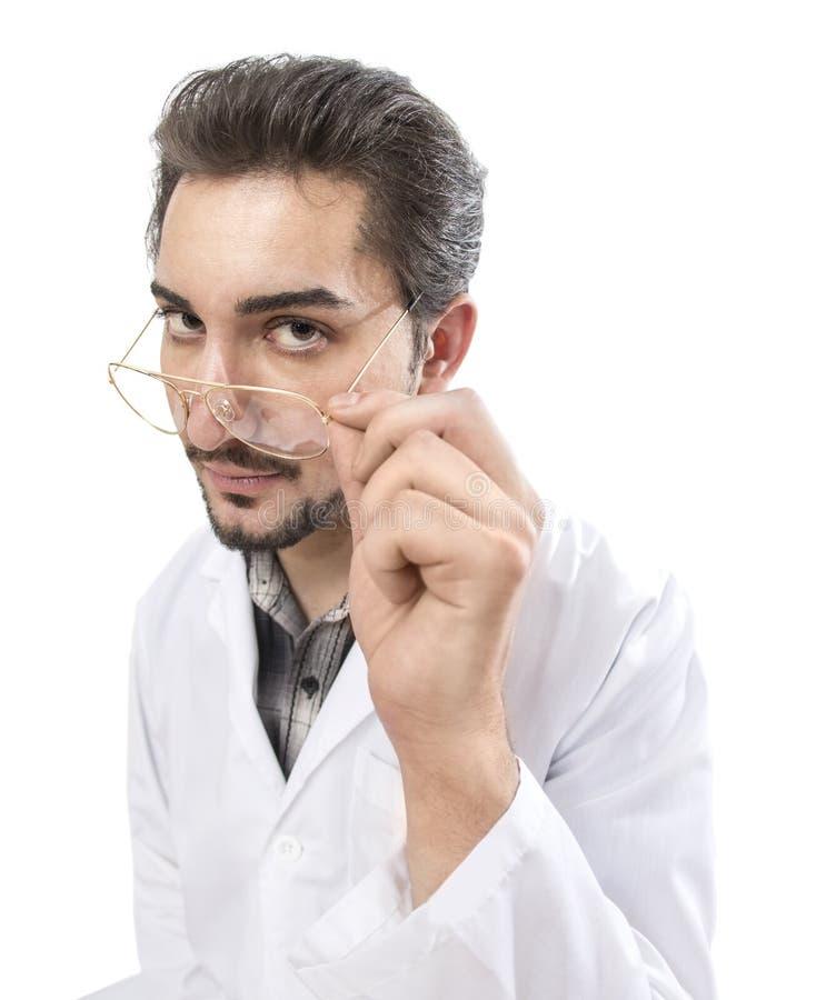 Ett gyckelskott av en säker person i ett labblag som ser till och med hans exponeringsglas med bekräftelse och sakkunskap arkivfoto