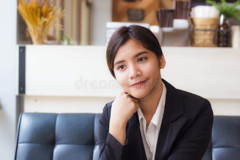 Ett härligt asiatiskt sammanträde för affärskvinna på soffan och se eller tänka något med hennes le royaltyfri foto