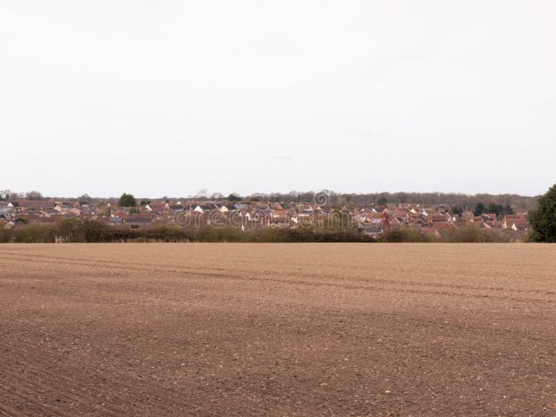 Ett härligt brunt fält med en sikt av staden i avståndet royaltyfri bild
