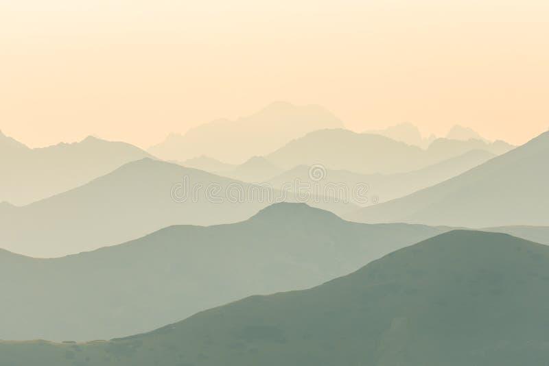 Ett härligt, färgrikt abstrakt berglandskap i soluppgång Minimalist landskap av berg i morgon i blåa signaler arkivfoto
