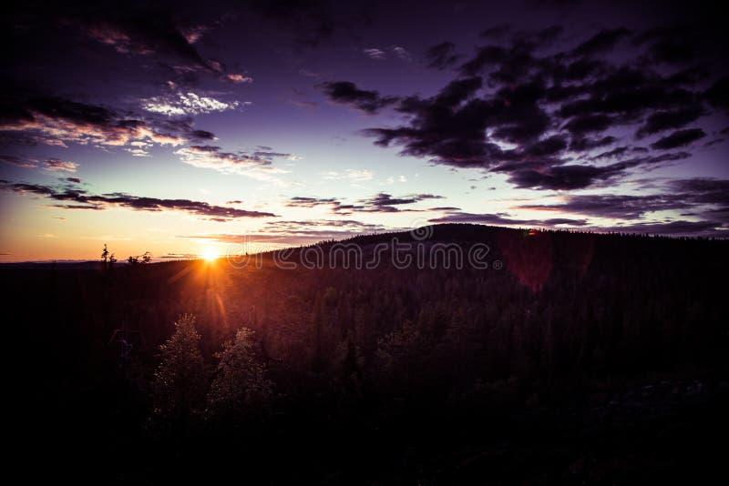 Ett härligt landskap med en midnatt sol ovanför arktisk cirkel arkivbild