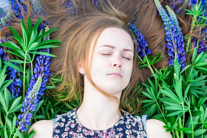 Ett härligt och en ung flicka ligger på en överkast av blommor, håller ögonen på kopplar av hon och i strålarna av solen arkivfoton