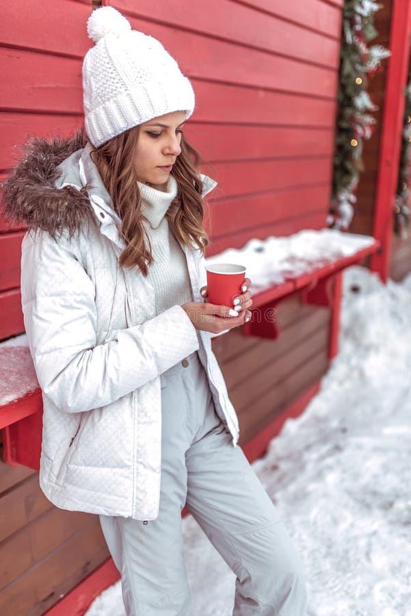 Ett härligt och en ung flicka värme om rånar och att rymma koppen med varmt kaffe eller te i hennes händer I en varm vit royaltyfria foton