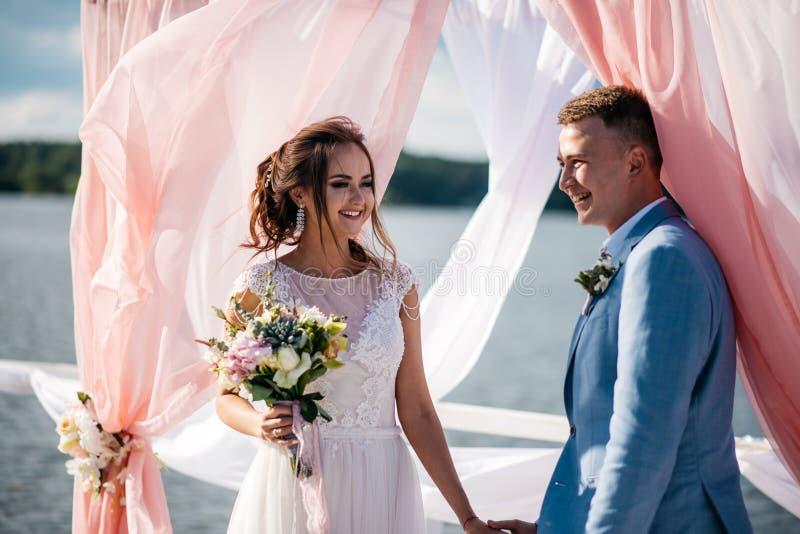 Ett härligt och lyckligt par, bruden och brudgum, ställning på pir under bröllopbågen royaltyfri bild