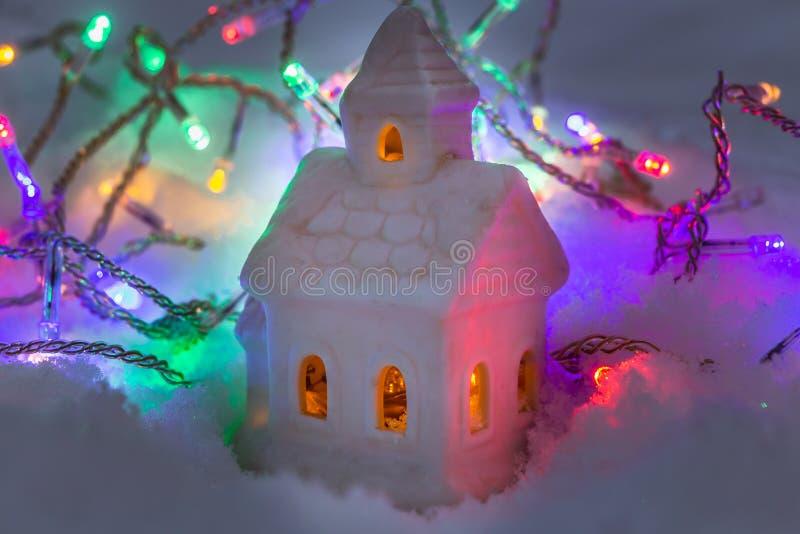 Ett härligt sagolikt litet vitt hus med gula ljus i fönstren och girlanderna av att bränna färgrika lampor på en vit snö royaltyfri foto